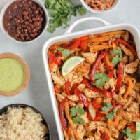oven baked fajitas in a white baking dish with fajita ingredients in separate bowls around fajita bake