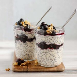 two mason jars filled with overnight oats with chia seeds and blueberries