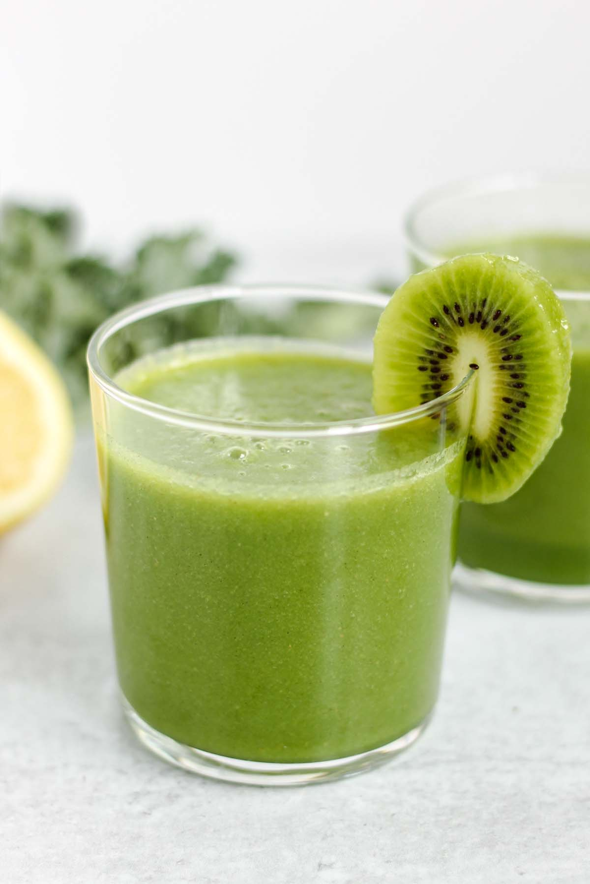 Small glass filled with kale apple smoothie with a kiwi slice on the rim of the glass.
