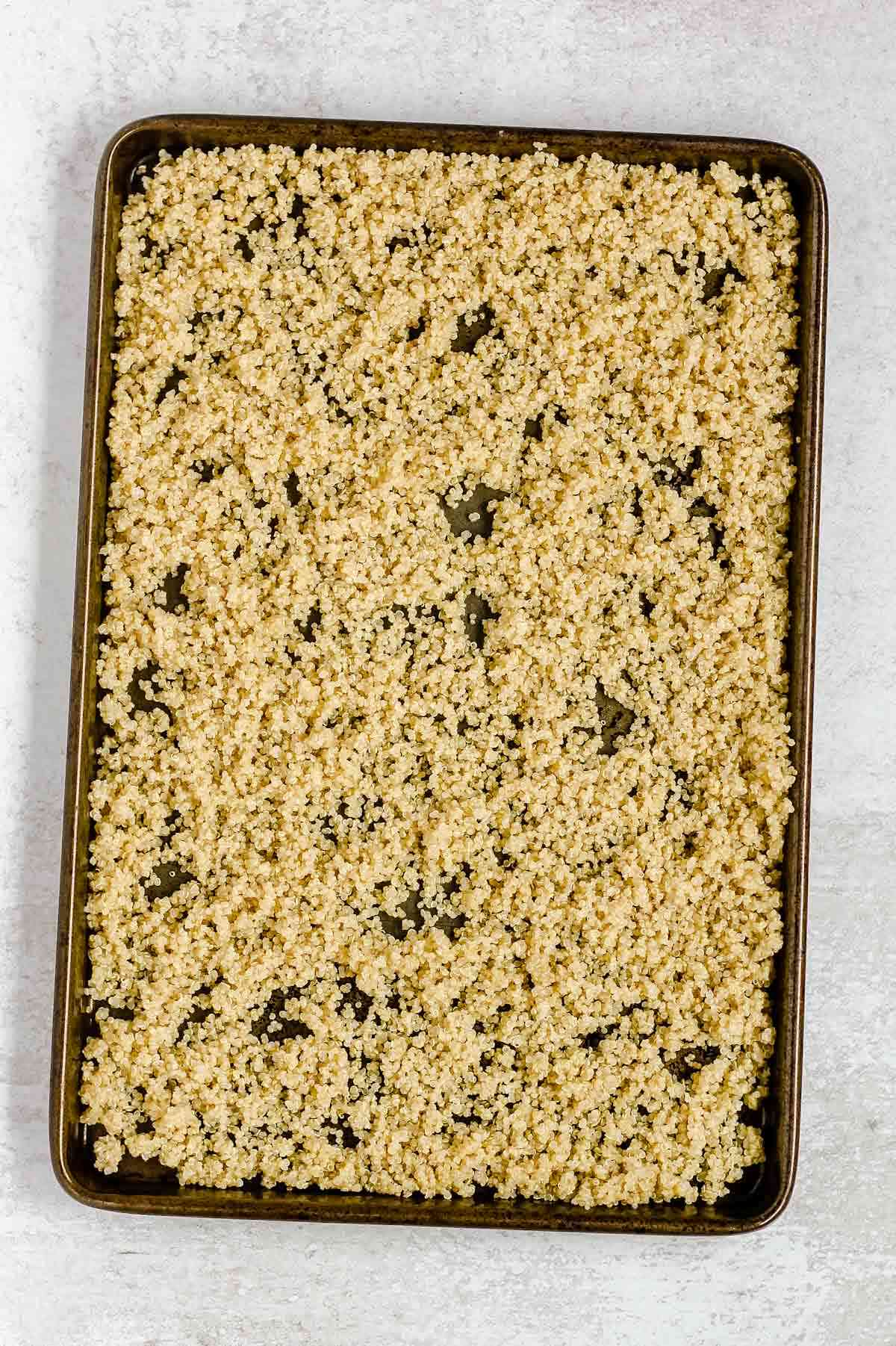 Cooked quinoa on a cookie sheet.