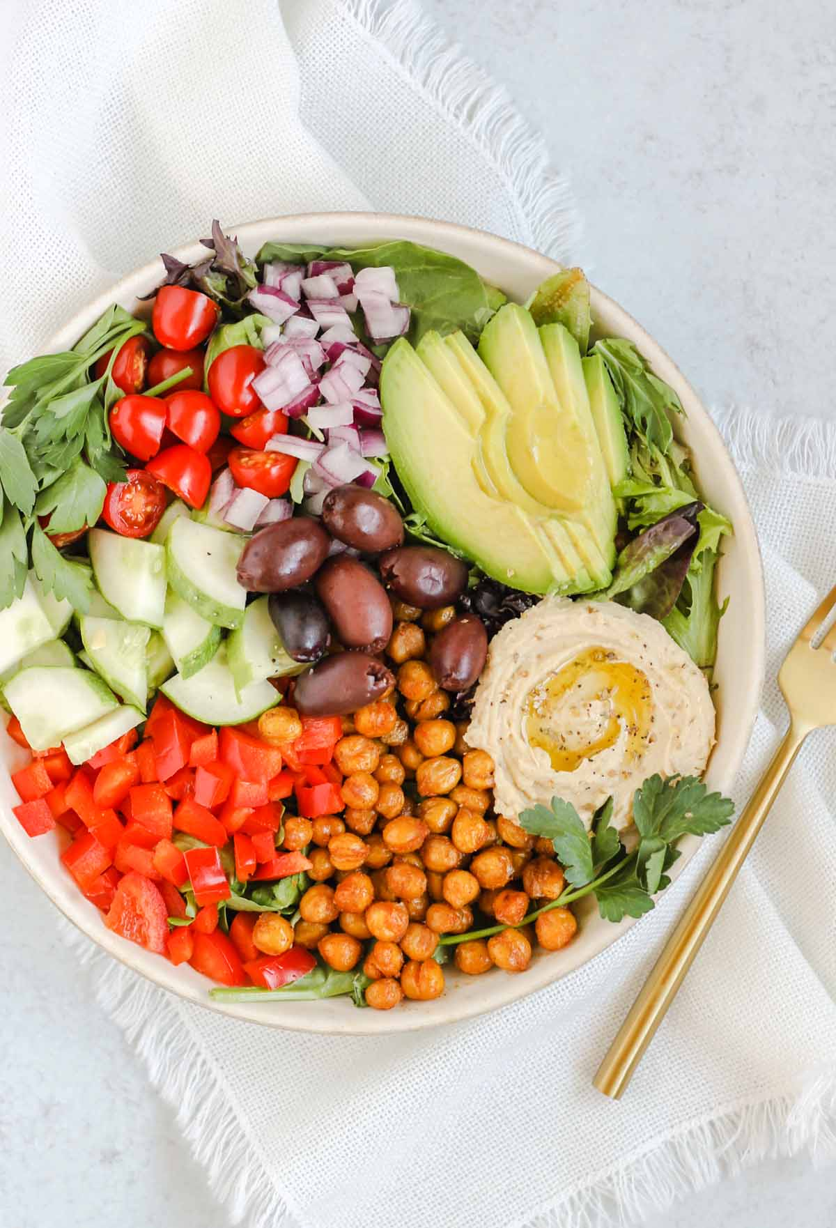 Mediterranean salad in a white bowl with a gold fork.