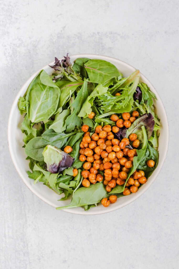 Mixed greens and roasted chickpeas in a salad bowl.