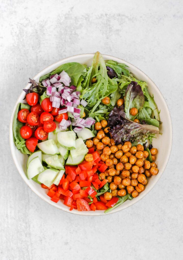 Mixed greens, roasted chickpeas, peppers, cucumbers, tomatoes, and onions in a salad bowl.