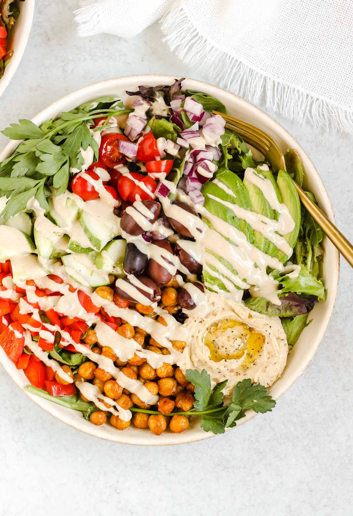 Mediterranean salad bowl with tahini dressing drizzled on top.