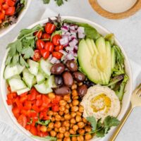 Mediterranean salad in shallow salad bowl with side of tahini dressing.