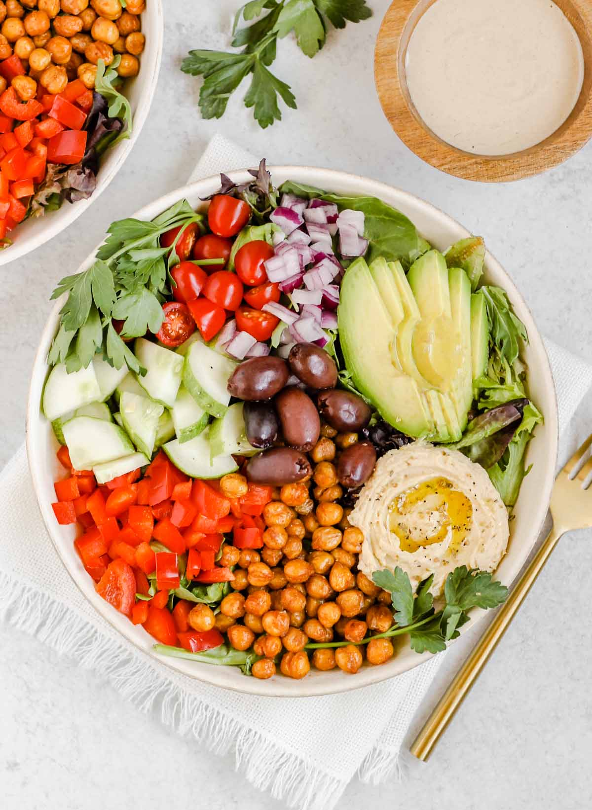 Mediterranean salad in a white bowl with a gold fork and a side of tahini dressing.