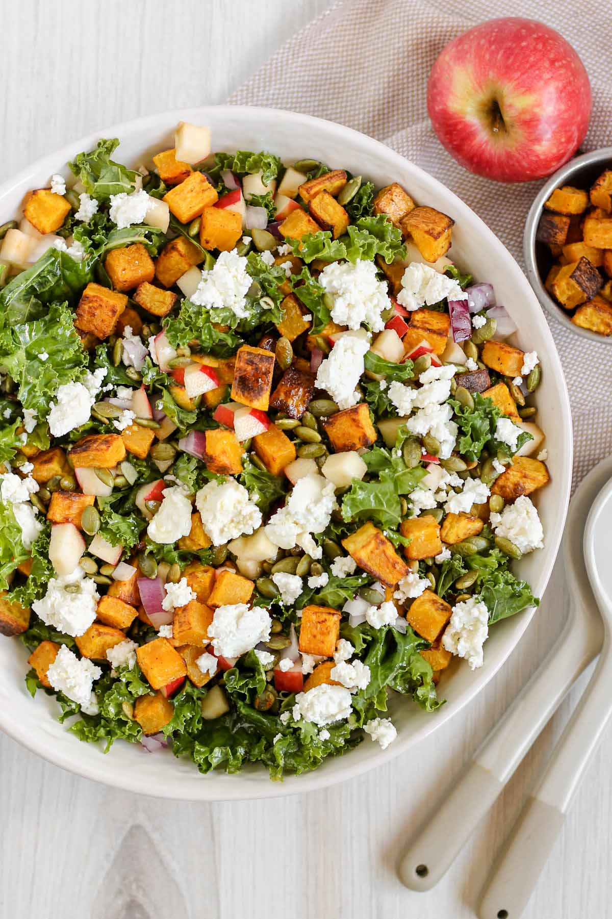 Kale salad with butternut squash and goat cheese in a large serving bowl.
