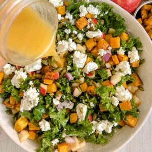 Dressing being poured on kale salad with butternut squash.