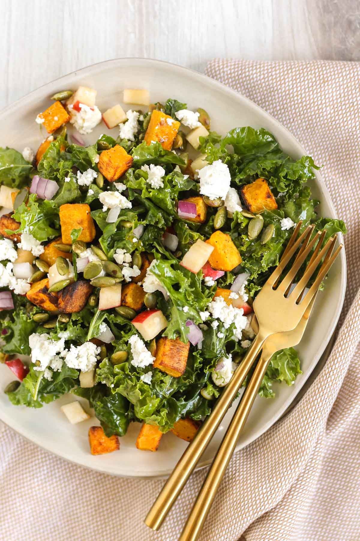 Small salad plate with butternut squash kale salad and a gold fork.