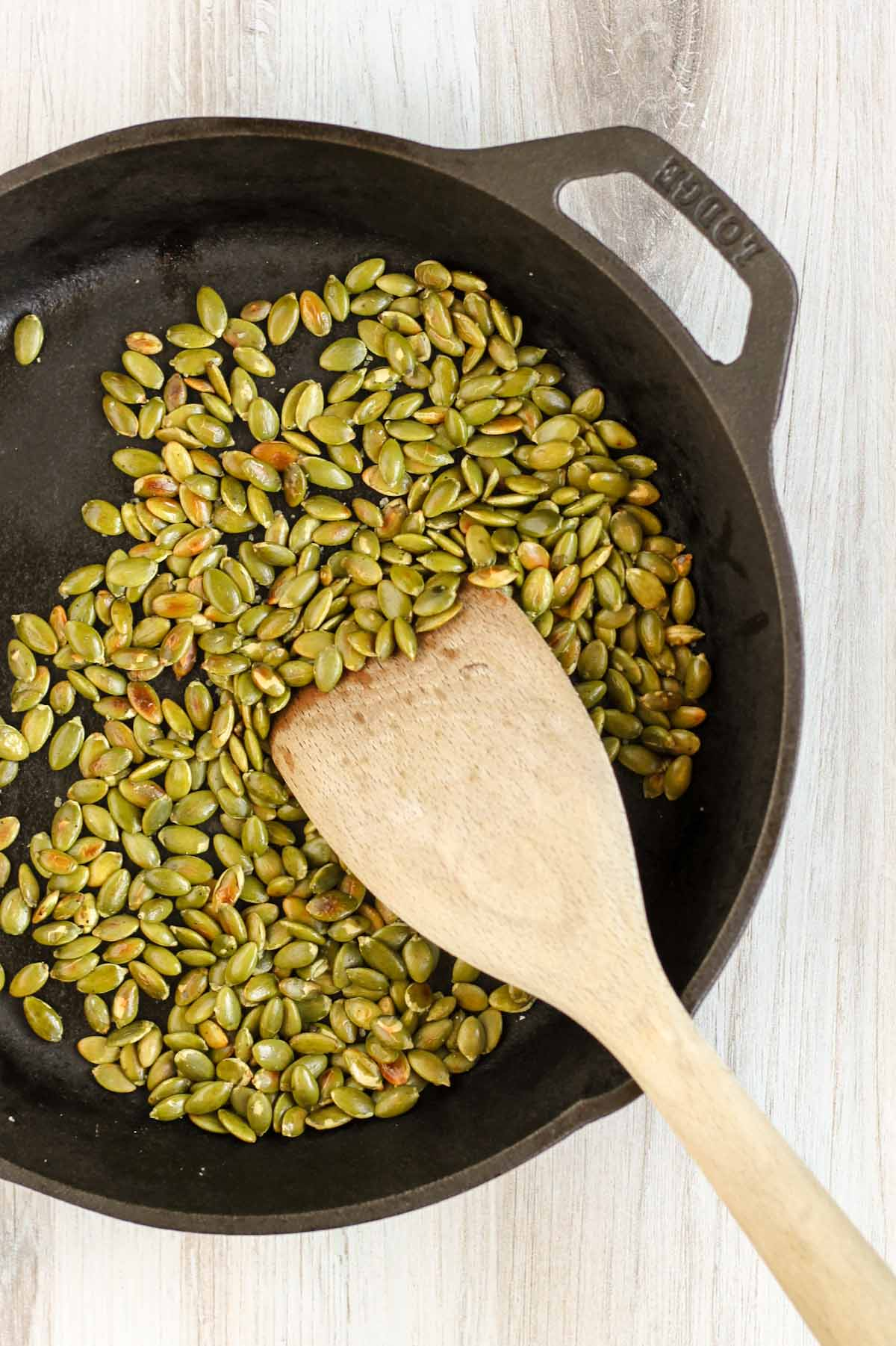 Roasted pumpkin seeds in a cast iron skillet.