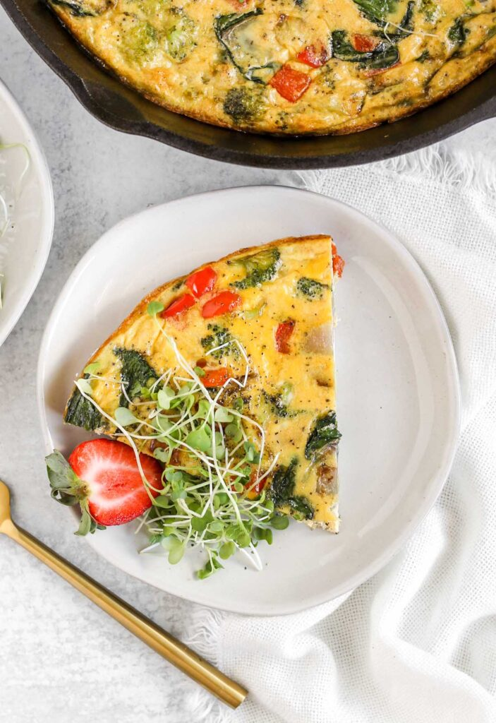 A piece of vegetable frittata on a small white plate.