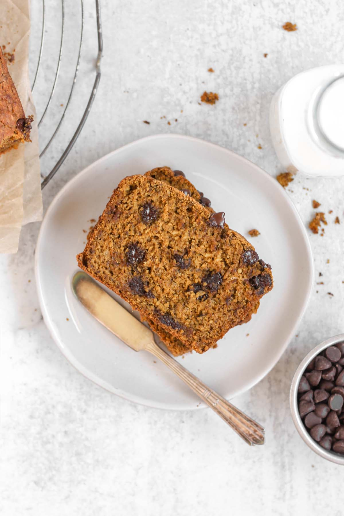 Overhead view of a piece of gluten-free pumpkin chocolate chip bread on a white plate.