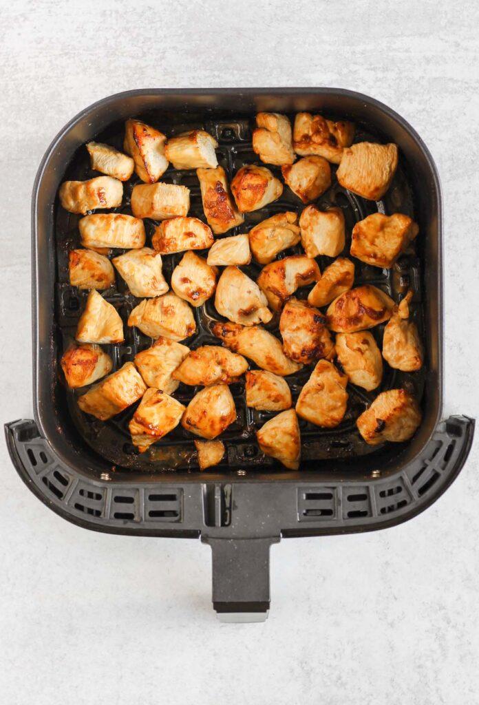 Cooked teriyaki chicken pieces in air fryer basket.