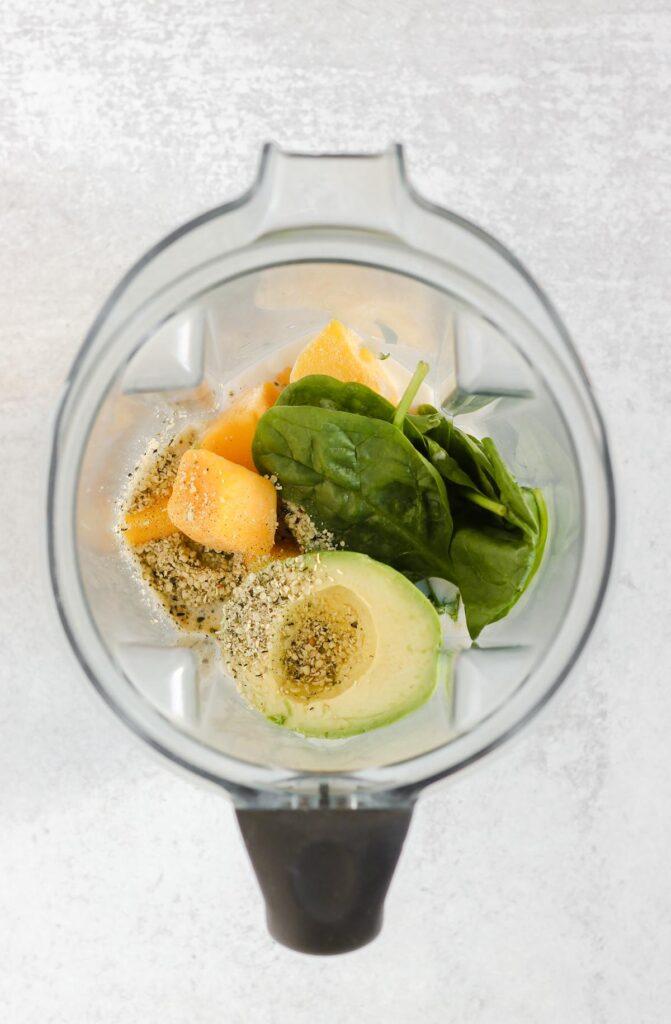 Avocado, mango, spinach, hemp, and milk in a blender.