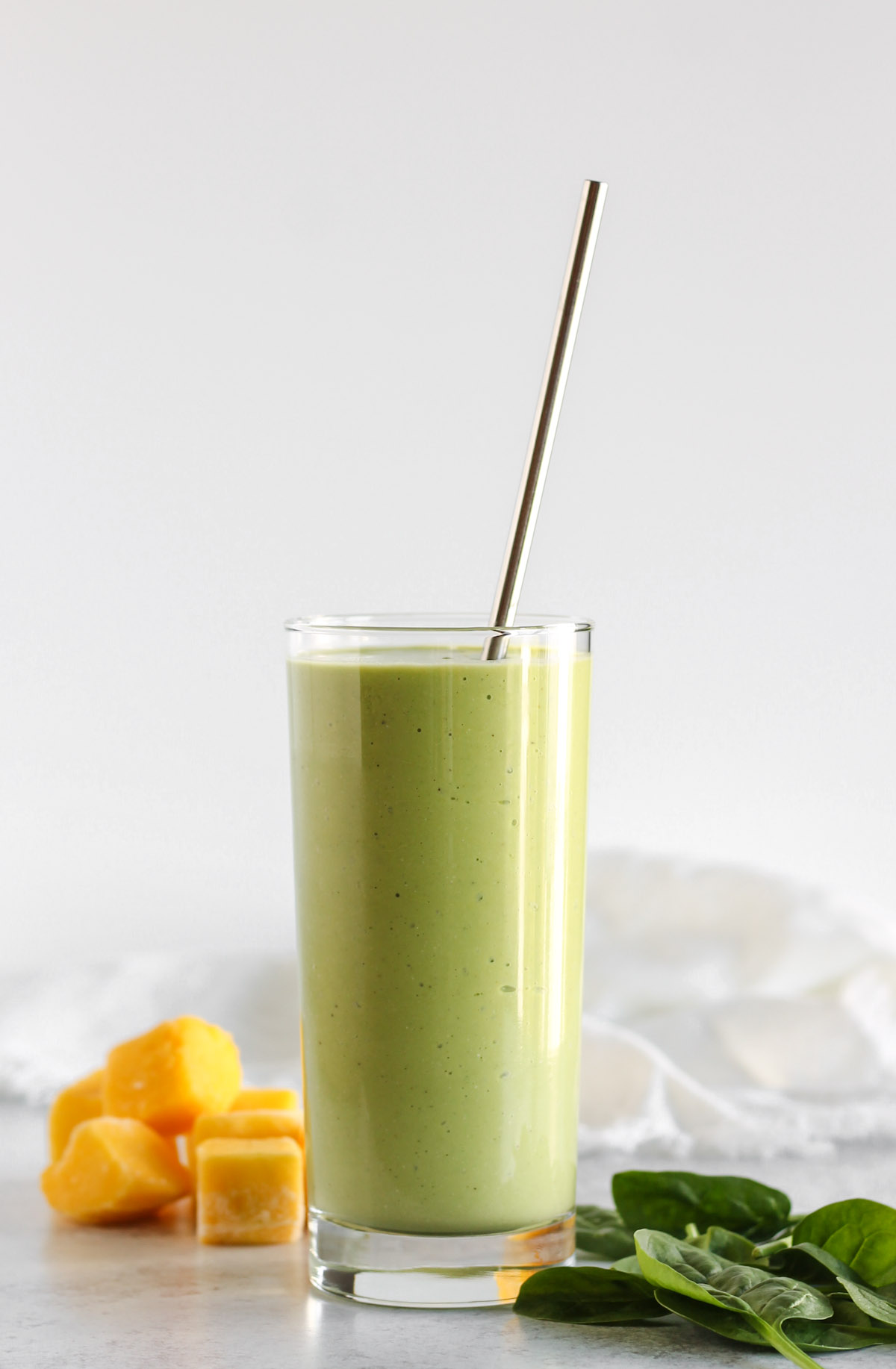Spinach mango smoothie in a tall glass with a stainless steel straw.