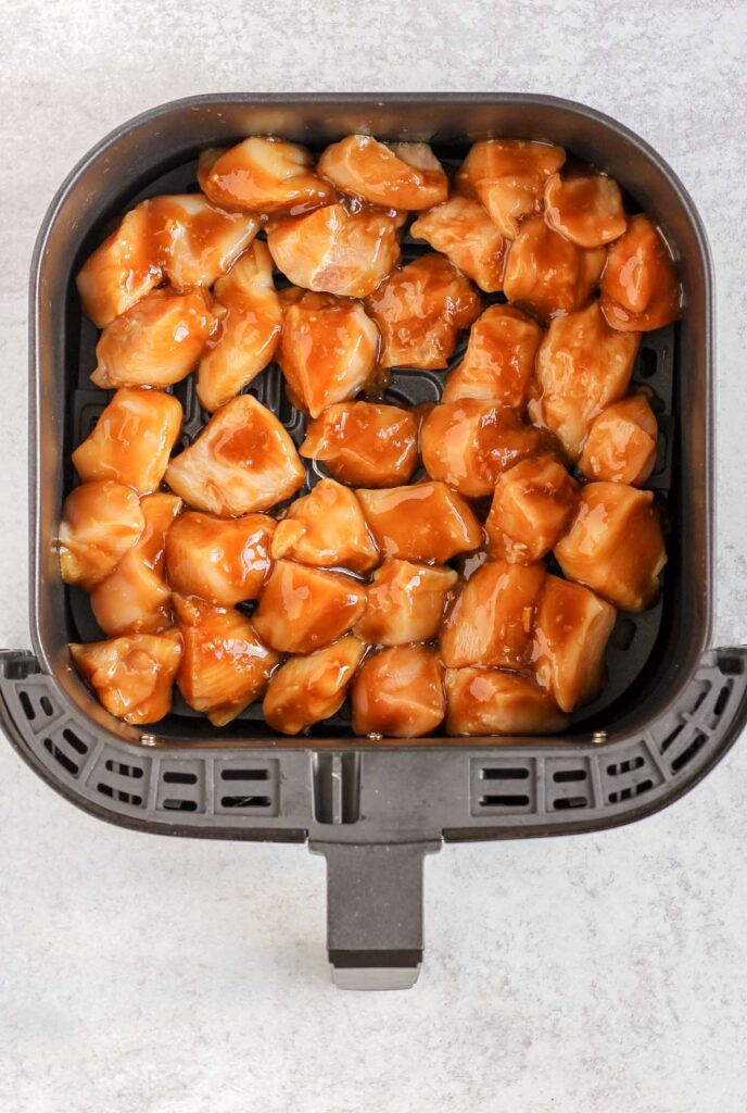Raw chicken coated with teriyaki sauce in air fryer basket.